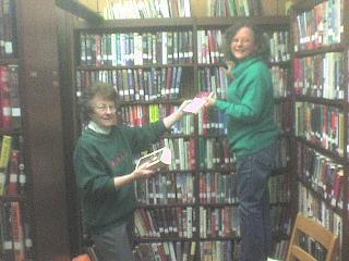Volunteers help put books away.